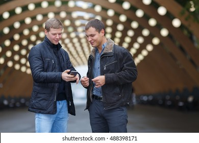 two young man in black jacket on background of lights installation main park alley, look in phone and smiling