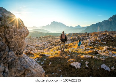 two young man enjoying the view of the mountains landscape in the dolomites national park, south tyrol