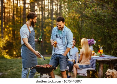 Two young man making barbecue outdoors