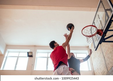 Two young man playing basketball indoors