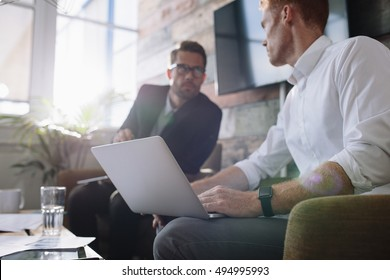 Two young man sitting in office and discussing business. Businessman with laptop talking with colleague during meeting.