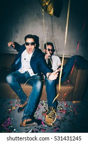 Two young man sitting at a party, having a great time.
