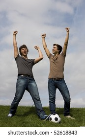Two young man with a soccer ball celebrate