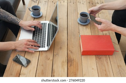 two young man using laptop and a smartphone.focus on the hand