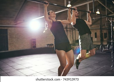 Two young man and woman in sportswear doing pull-ups in gym.