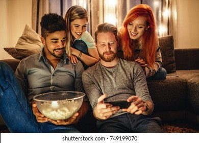 Two young man and two young women looking at a mobile phone