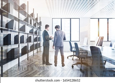 Two young managers discussing work in stylish panoramic open space office with white walls, wooden floor, white computer desk and window with blurry view. Toned image