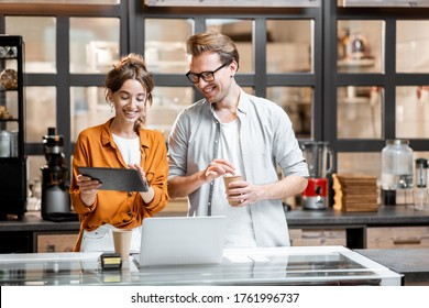 Two young managers or shop owners having some discussion while standing with a digital tablet at the counter of the shop or cafe. Small business management concept