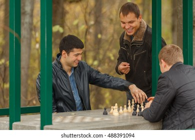 Two young men in black jackets playing chess, outdoors in park, third man watching them play, white pieces go
