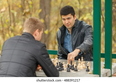 Two young men in black jackets playing chess outdoors in park, white pieces go