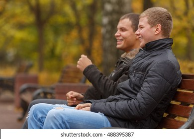 Two young men in black jackets sitting on bench in park and laughing, side view