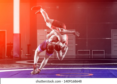 Two young men in blue and red wrestling tights are wrestlng and making a suplex wrestling on a wrestling carpet in the gym. The concept of fair wrestling