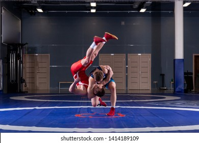 Two young men in blue and red wrestling tights are wrestlng and making a hip throw on a yellow wrestling carpet in the gym. The concept of fair wrestling