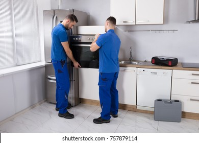 Two Young Men In Blue Uniform Fixing Oven In Kitchen