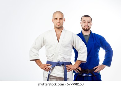 Two young men in a blue and white kimono for judo, jujitsu posing on isolated white background