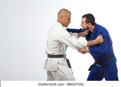 Two young men in a blue and white kimono doing a judo shot,  fight judo , Jiu Jitsu on an isolated white background