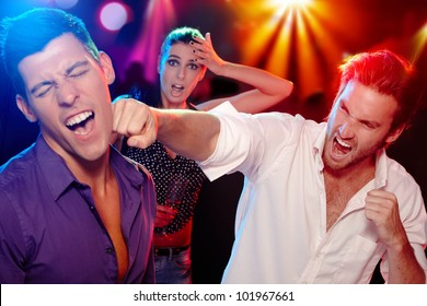 Two young men bopping in the nightclub for a woman, who is looking worried at background.