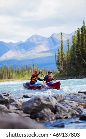Two young men canoeing a whitewater river in the far north of North America.