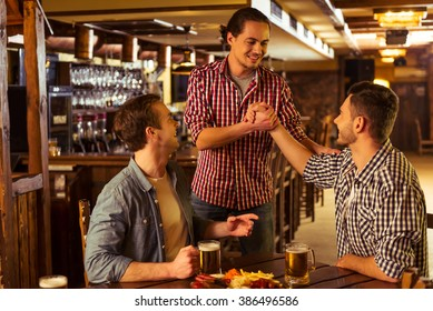 Two young men in casual clothes are smiling, talking, drinking beer and greeting their friend while sitting in pub