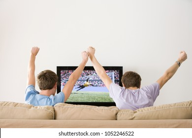 Two young men cheering at football on the tv