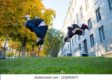 Two young men doing a side flip or somersault while they practicing parkour on the street.