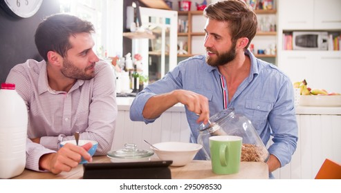 Two Young Men Eating Breakfast In Kitchen Together