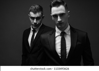 two young men in elegant suits posing. Business style. Male beauty, fashion. Hairstyle.
