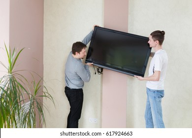 Two young men fitting TV with flat screen television to the wall. Repair and relocation concept