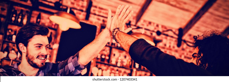 Two young men giving high five to each other in pub