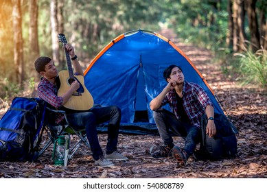 Two young men with guitars sitting beside a tent camp in the woods.