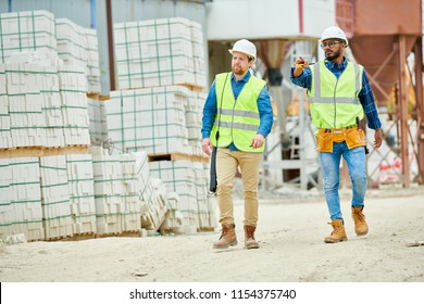 Two young men in hardhats and waistcoats pointing at distance while walking near stacks of building materials during inspection on construction site