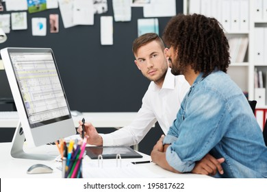 Two young men having a business meeting with an African American sitting looking at information on the computer watched closely by his colleague