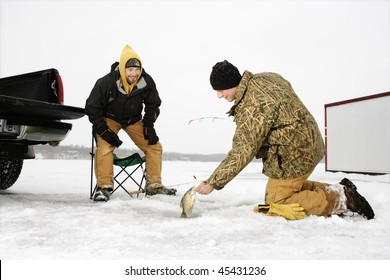 Two young men ice fishing in a winter environment. Horizontal shot.