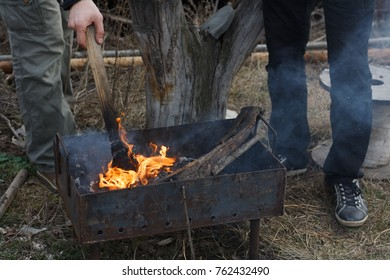 Two young men ignite the wood in the grill, going to fry a shish kebab.
