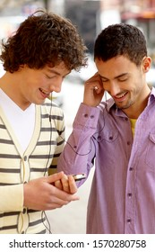 Two young men listening to music on mp3 player