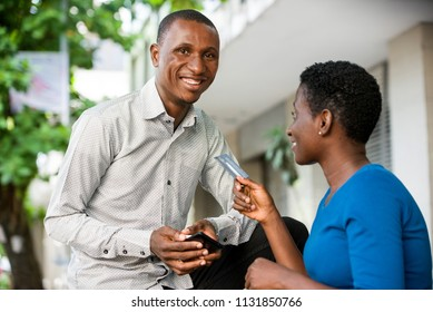 two young men man and woman talking outside.Young woman sitting back with outstretched hand hold a credit card.