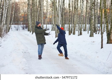 Two young men on a walk in winter Park. One of them slipped and lost his balance, waving his arms, falls back, his friend wants to support it.