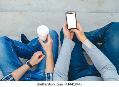 Two young men with the phone in his hand sitting on the steps. top view