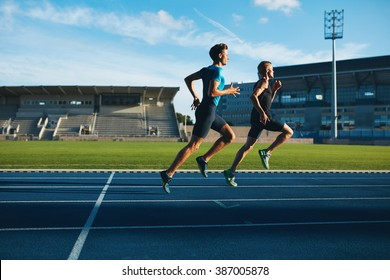 Two young men running on race track. Male professional athletes running on athletics race track.