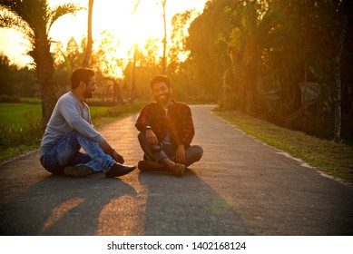 Two young men smiling together sitting on a street in the afternoon