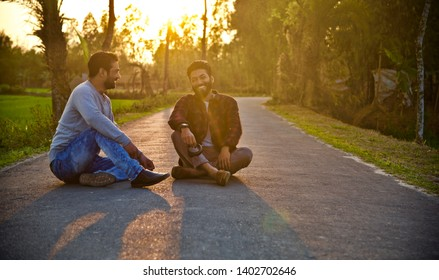 Two young men smiling together sitting on an empty street
