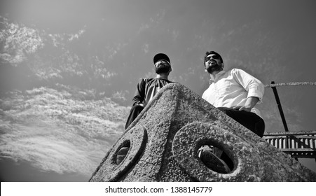 Two young men standing on a parts of an old metallic boat