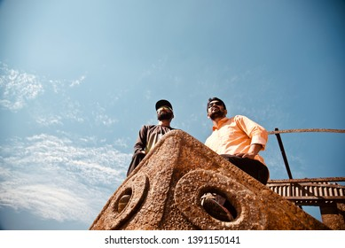 Two young men standing on an abandoned metallic boat