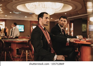 Two young men in suits behind table in a casino