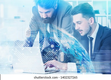Two young men in suits working in office with laptop. Double exposure of planet and circuit interface. Concept of hi tech and engineering. Toned image. Elements of this image furnished by NASA