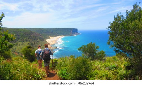 Two young men trekking through the Royal National Park, near Sydney Australia with sticks and backpacks on with a lovely view of Gerai Beach ahead on top of a hill track