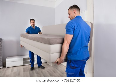 Two Young Men In Uniform Holding Sofa In Living Room