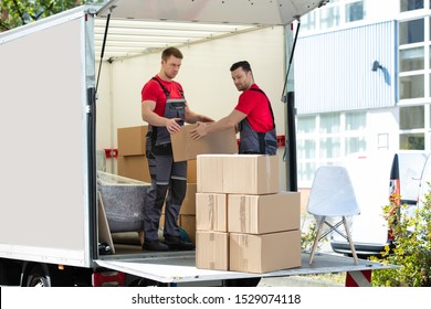 Two Young Men Unloading And Stacking The Brown Cardboard Boxes On Moving Truck