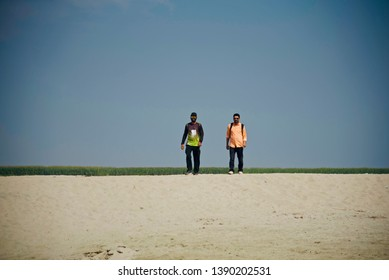 Two young men walking together around a coastal area