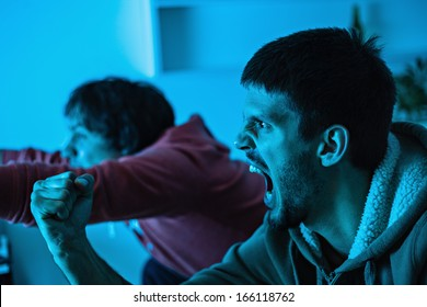 Two young men watching sports competition and drinking beer.